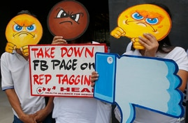 "FILE - People covering their faces with ""angry emoji"" cutouts protest Facebook's alleged inaction against fake news, hate speech and red-tagging of activists, in suburban Taguig city, east of Manila, Philippines, May 9, 2019."