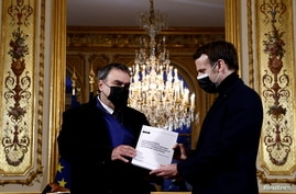 FILE - French President Emmanuel Macron meets historian Benjamin Stora for the delivery of a report on Algeria's colonization and war, at the Elysee Palace in Paris, France, Jan. 20, 2021.