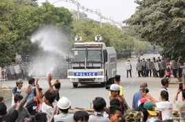 Police officers confront people protesting against the military coup, in Mandalay, Myanmar, Feb. 20, 2021.