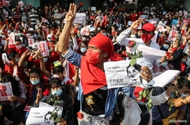People show the three-finger salute and hold signs demanding the release of elected leader Aung San Suu Kyi as they take part in a protest against the military coup, in Yangon, Myanmar, Feb. 7, 2021