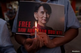 A demonstrator holds a placard and a candle during a protest against the military coup in Yangon, Myanmar, Feb. 16, 2021.