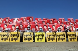 Demonstrators hold placards with the image of Aung San Suu Kyi during a protest against the military coup, in Naypyitaw, Myanmar, Feb. 15, 2021.