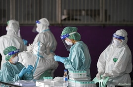 Healthcare workers get ready to collect samples during proactive testing of migrant workers at their work place, amid the spread of the COVID-19 outbreak in Samut Sakhon province in Thailand, Jan. 27, 2021.