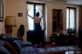 EDITORS NOTE: Graphic content / Mexican sex worker, Alenca, looks through her window before starting her working day at her…