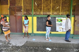Masked voters stand in line before casting their ballots in Jamaica's St. Catherine north central constituency during the general election, September 3,2020.