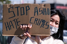 A demonstrator wearing a face mask and holding a sign takes part in a rally to raise awareness of anti-Asian violence, near…