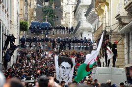 Algerian security forces form a human barrier as anti-government protesters take to the streets of the capital Algiers as the …