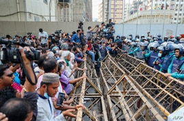 Activists stand separated from the police with a barrier during a protest against Digital Security Act (DSA), in Dhaka on March…