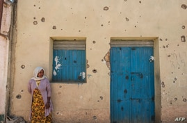 A woman leans on the wall of a damaged house which was shelled as federal-aligned forces entered the city, in Wukro, north of…