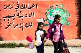 Syrian children cross a road in front of a mural awareness campaign drawing calling on people to take care as the COVID-19…