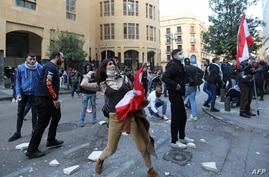 A Lebanese demonstrator hurls rocks over a fortified gate, leading to the Lebanese Parliament building, in downtown Beirut on…