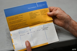 A woman shows her vaccination record at Zinga Zanga village hall vaccination centre in Beziers, southern France, on March 17,…