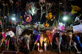 Flowers are laid along the perimeter fence outside a King Soopers grocery store in Boulder, Colorado on March 23, 2021, one day…