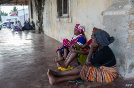 People wait on the outskirts of the seaport of Pemba on March 30, 2021 for the possible arrival of their families evacuated…