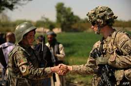 A US soldier from 1st Regiment 320 Field Artillary 101st Airbourne (R) shakes hands with a Afghan National Army (ANA) soldier…