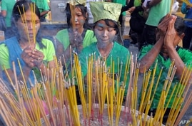 """Cambodian villagers with their faces painted to resemble the forest people from the film """"Avatar"""" pray during a rally against…"""