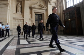 FILE - Police patrol inside the Paris courthouse.