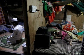 FILE - Rohingya refugee Shahid Hussain, 10, offers prayers after Iftar (breaking fast) time as his sister Sania, 2, sleeps.