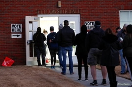 Voters line up early in the morning to cast their ballots in the U.S. Senate run-off election, at a polling station in Marietta.
