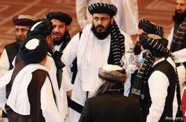 FILE PHOTO: Taliban delegates speak during talks between the Afghan government and Taliban insurgents in Doha, Qatar September…