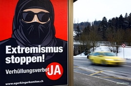 """A poster of the initiative committee against wearing the Burka (Verhuellungsverbot) reading """"Stop extremism! Veil ban -Yes"""" is…"""
