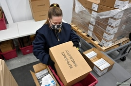 An employee with the McKesson Corporation places a package of the Johnson & Johnson COVID-19 vaccine into a transport container…