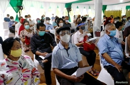 People wearing protective masks and face shields sit as they queue before receiving a dose of China's Sinovac Biotech vaccine…