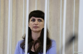 Journalist Katerina Borisevich sits inside a defendants' cage during a court hearing in Minsk, Belarus March 2, 2021. A…