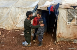 FILE PHOTO: Ahmad Hamra, is pictured with his children outside of a tent at an internally displaced Syrian camp, in northern…