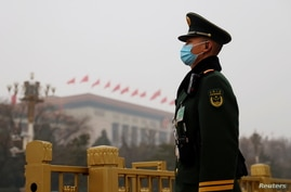 A paramilitary police officer stands guard near the Great Hall of the People before the opening session of the National People…