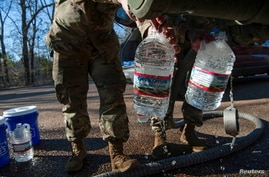 National Guard sergeants fill gallons for a resident at a public water distribution site after a recent bout of cold weather…