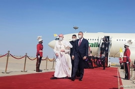 Iraqi Prime Minister Mustafa Al-Kadhimi walks with Pope Francis upon his arrival at Baghdad International Airport, in Baghdad.