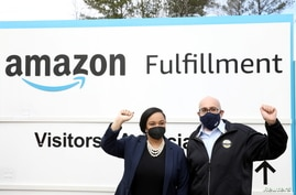 U.S. Rep. Nikema Williams and RWDSU President Stuart Appelbaum pose for a picture at the entrance to Amazon facility as they…