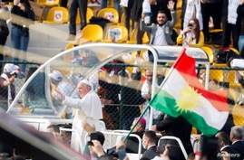 A Kurdistan flag is held up as Pope Francis arrives to hold a mass at Franso Hariri Stadium in Erbil, Iraq, March 7, 2021…