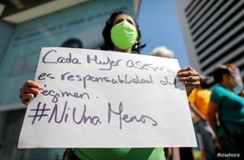 A woman holds a placard as Venezuelan human rights activists protest to demand the release of 17 women they consider political prisoners, as well as to demand punishment for perpetrators of femicide, in Caracas, Venezuela, March 8, 2021.