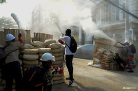 Anti-coup demonstrators sprays fire extinguishers over a barricade during a protests in Yangon, Myanmar, March 9, 2021.