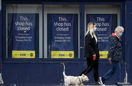People wearing face masks walk past a closed retail unit in Preston, Britain, March 9, 2021. REUTERS/Phil Noble
