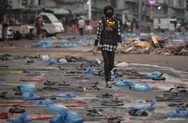 A protester walks in a street full of water bags to be used against tear gas, during an anti-coup protest at Hledan junction in Yangon, Myanmar, March 14, 2021.