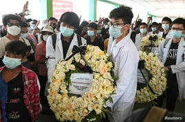 People carries a wreath, as they attend the funeral of Khant Nyar Hein, 17 years old medical student who was shot and killed…