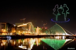 "A display by Tourism Ireland entitled ""Orchestra of Light"" featuring a swarm of 500 drones is animated in the night sky above the Samuel Beckett bridge on the river Liffey for St Patrick's Day, as it is cancelled for the second year in a row due to COVID-19, Dublin, March 7, 2021."