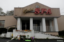 Flowers and a poster are left outside Gold Spa following the deadly shootings in Atlanta, Georgia, U.S. March 17, 2021. REUTERS…
