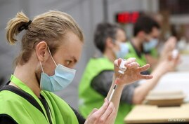 Medical workers prepare doses of Oxford/AstraZeneca's COVID-19 vaccine at a vaccination centre in Antwerp, Belgium March 18,…