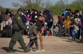 A U.S. Border Patrol Agent escorts two asylum-seeking unaccompanied minors from Central America as others take refuge near a…