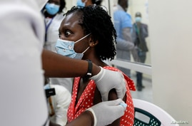 FILE - A woman reacts as she receives the AstraZeneca/Oxford vaccine under the COVAX scheme against coronavirus disease (COVID-19) at the Kenyatta National Hospital in Nairobi, Kenya, March 5, 2021.