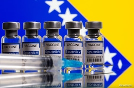 "FILE - Vials labelled ""Sputnik V coronavirus disease (COVID-19) vaccine"" and a syringe are seen in front of a displayed Bosnian flag in this illustration picture taken March 17, 2021."