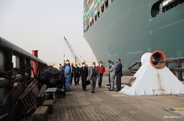 Osama Rabie, Chairman of the Suez Canal Authority, walks as he monitors the situation near stranded container ship Ever Given,…