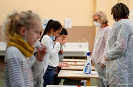 FILE - School children attend a COVID-19 saliva test in a primary school in Nice, France.