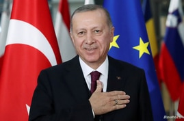 FILE PHOTO: Turkish President Tayyip Erdogan reacts ahead of a meeting with EU Council President Charles Michel pose in…