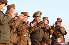 Ri Pyong Chol, the senior leader who is overseeing the test, and other military officials applaud after the launch of a newly…