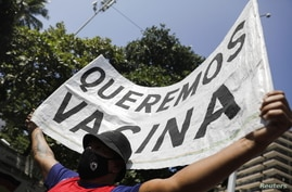 """A man holds a banner reading """"We want vaccine"""" during a protest against new measures implemented to curb the spread of the…"""